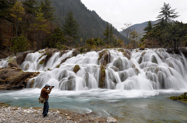 A photographer takes a picture of Shuanglonghai Waterfall, a new scenic spot formed after the earthquake in Jiuzhaigou, Sichuan province, in November. (Hua Xiaofeng/for China Daily)